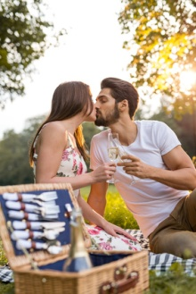 Closeup of an affectionate young couple kissing and having champagne outdoors.
