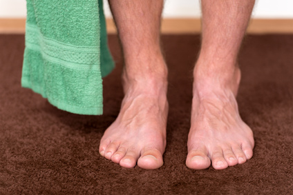 Healthy male feet with towel stepping towards the bathroom.